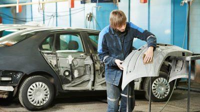 Collision repair technician installing used car part
