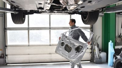 Auto collision repairer carrying car door (view from under lifted car)