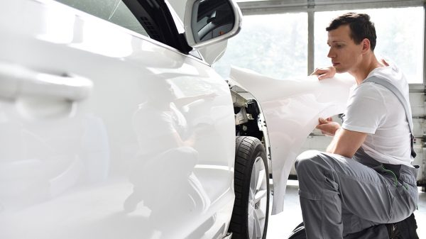 Collision repair technicians with vehicle