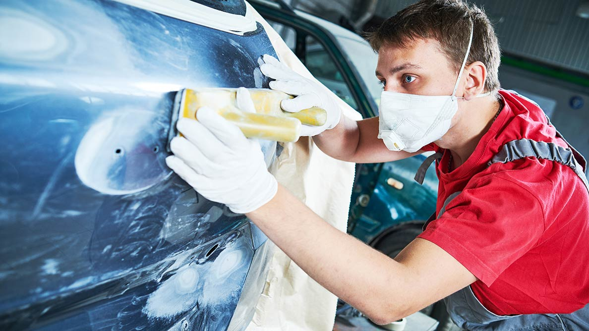 Young man with bright red shirt sanding a car panel in collision centre