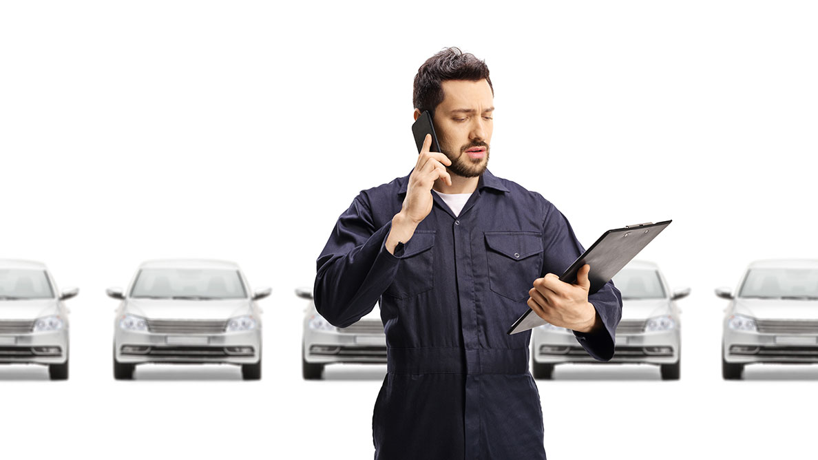 Perplexed man with clipboard in front of parked cars